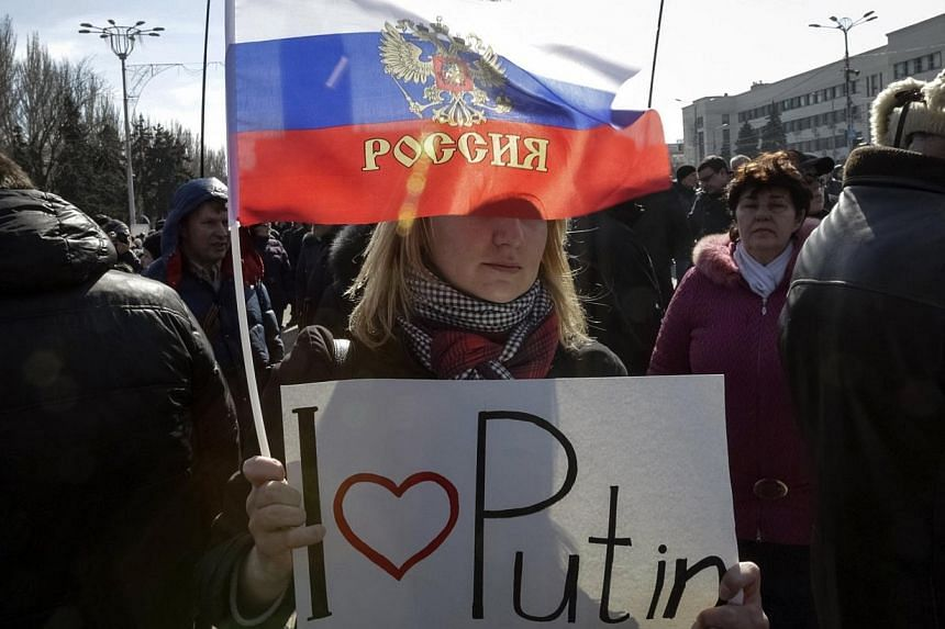 Pro-Russian demonstrators take part in a rally in central Donetsk on March 8, 2014.Russian flags flooded Lenin Square in the centre of Crimea's capital Simferopol on Sunday, March 9, 2014, as thousands rallied in support of Moscow's takeover of
