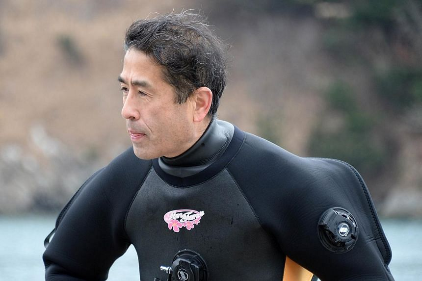 Yasuo Takamatsu looks out to sea as he sits on the edge of a boat after a diving lesson in Onagawa, Miyagi Prefecture on March 2, 2014.-- FILE PHOTO: AFP