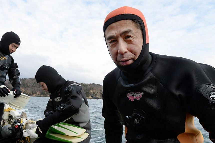 Yasuo Takamatsu (right) speaks to an AFP reporter beside his instructors as he sits on the edge of a boat after diving in the ice-cold sea water in Onagawa, Miyagi Prefecture on March 2, 2014.-- FILE PHOTO: AFP