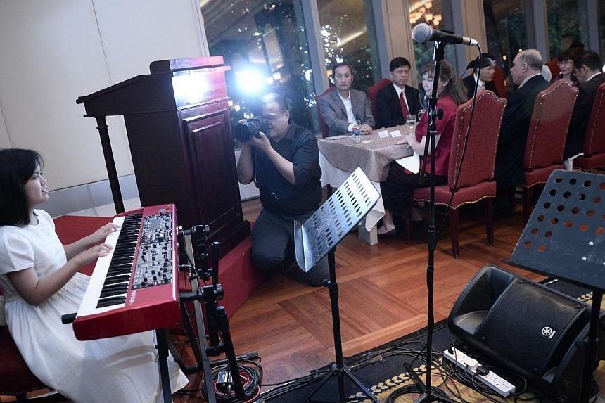 Adelyn Koh, 12, who is visually handicapped, performs a piano piece during the fundraising dinner held by Clearvision for The Singapore Association of the Visually Handicapped on 9 March, 2014. -- ST PHOTO: MARK CHEONG
