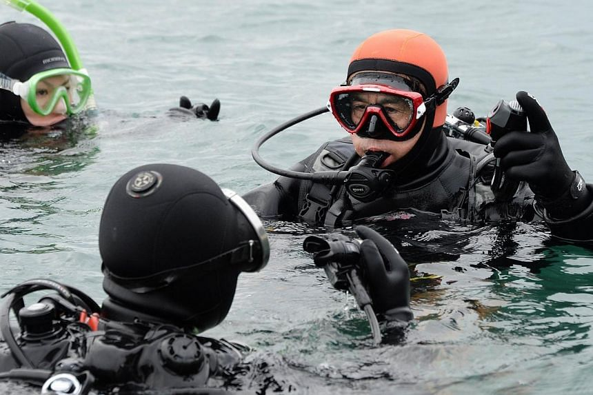 Yasuo Takamatsu (right) listens to his instructor in the ice-cold sea water in Onagawa, Miyagi Prefecture on March 2, 2014. -- FILE PHOTO: AFP