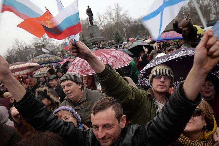 Pro-Russian supporters wave Russian flags during a mass pro-Russian rally in the center of Sevastopol on March 8, 2014.Thousands took to the streets for rival pro- and anti-Kremlin rallies across Ukraine on Sunday, March 9, 2014, as the West an