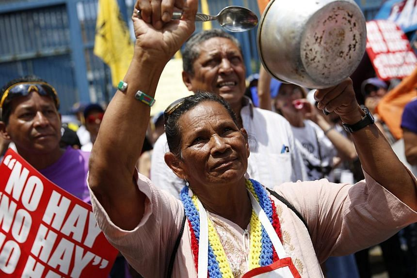 An anti-government protester hits a pot during a march in Caracas, Venezuela, on March 8, 2014. -- PHOTO: REUTERS
