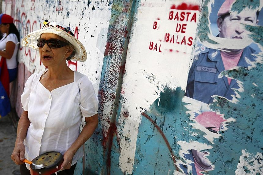 An anti-government protester hits a pot in front of a poster of late Venezuela's President Hugo Chavez during a rally in Caracas, Venezuela, on March 8, 2014. -- PHOTO: REUTERS