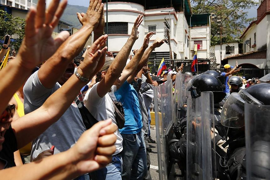 Anti-government protester raise their hands after the police attempt to stop their march in Caracas, Venezuela, on March 8, 2014. -- PHOTO: REUTERS