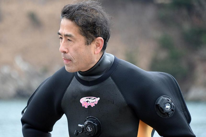 Mr Yasuo Takamatsu, 57, grunts with the effort of hoisting a scuba diving tank onto his back, as he prepares to step into the cold waters off Japan's tsunami-ravaged coast to look for the body of his wife, one of thousands still missing three years o