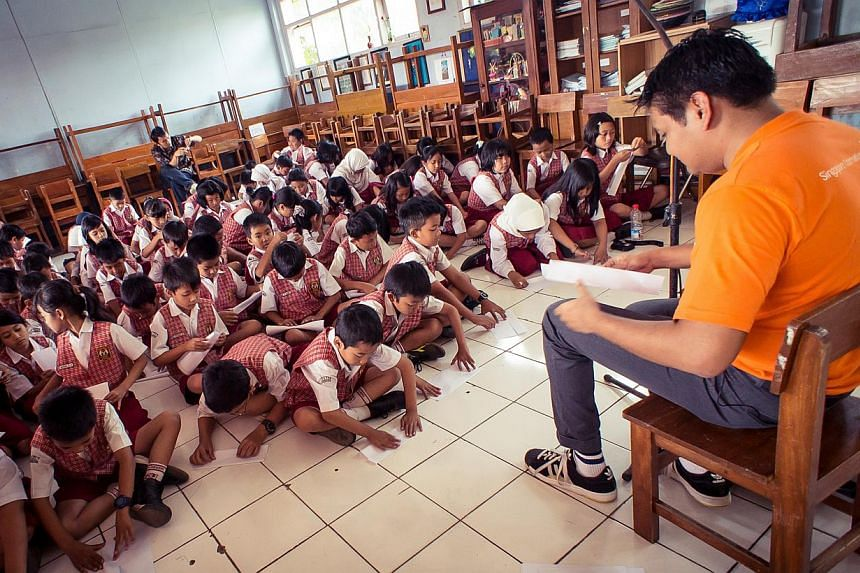 A volunteer from the Singapore International Foundation (SIF) conducting a storytelling session for children in Bandung, Indonesia as part of a Words on Wheels project. The number of people who go out of Singapore to volunteer has more than doubled f