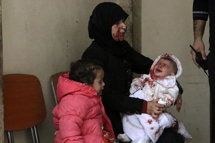 A woman survivor holds her crying baby in a hospital in Aleppo's al-Sakhour district, after what activists said was a barrel bomb dropped at Aleppo's Haydariye district by forces loyal to Syria's President Bashar al-Assad, on March 9, 2014. -- PHOTO: