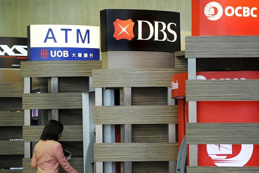 A customer uses a DBS Group Holdings Ltd. automated teller machine (ATM), standing between the ATMs of United Overseas Bank Ltd. and Oversea-Chinese Banking Corp. Ltd., at Changi Airport in Singapore, on Thursday, July 28, 2011. Making funds transfer