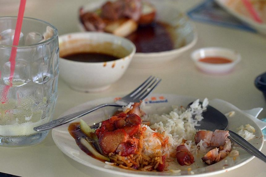 Unfinished food and drink left on a table at a hawker centre. Singapore needs to cut food waste and its food industry should share resources like procurement and equipment, to improve food security.-- ST PHOTO: KUA CHEE SIONG