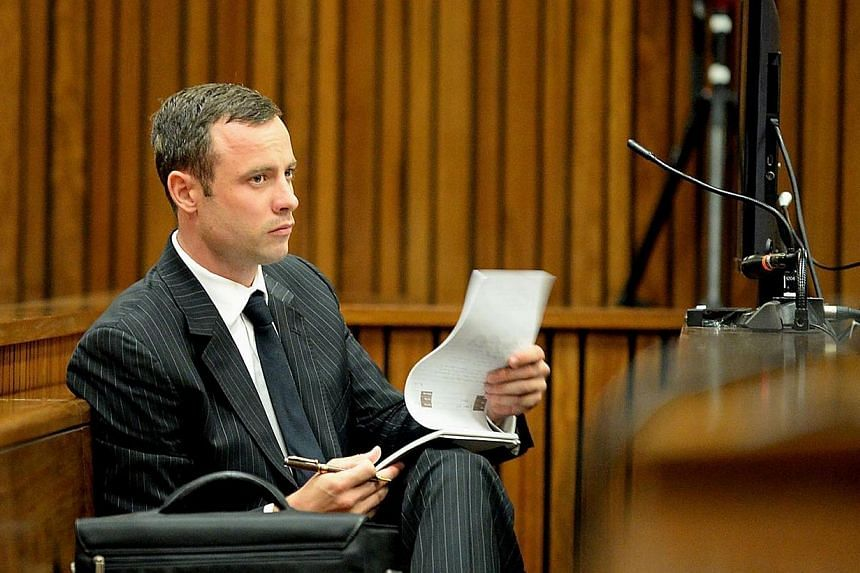 Olympic and Paralympic track star Oscar Pistorius waits prior to a hearing on the sixth day of his trial for the 2013 murder of his girlfriend, on March 10, 2014 at the high court in Pretoria. A South African court blocked all live broadcasts on Mond