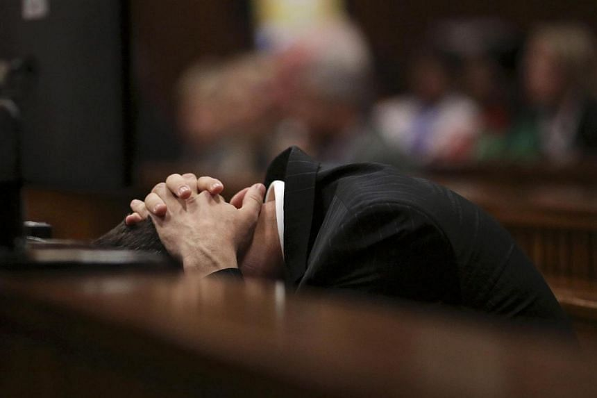 Olympic and Paralympic track star Oscar Pistorius in the dock with his hands over his head during his trial for the murder of his girlfriend Reeva Steenkamp at the North Gauteng High Court in Pretoria on March 10, 2014. -- PHOTO: REUTERS