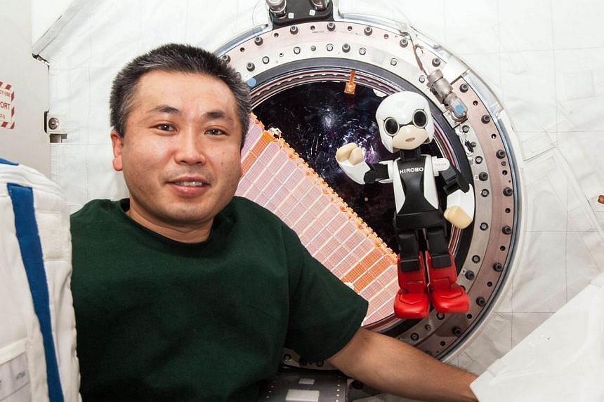 """This undated handout picture released from KIBO Robot Project on December 20, 2013 shows Japanese astronaut Koichi Wakata smiling with the humanoid robot """"Kirobo"""" in the International Space Station (ISS) in space. -- FILE PHOTO: AFP"""