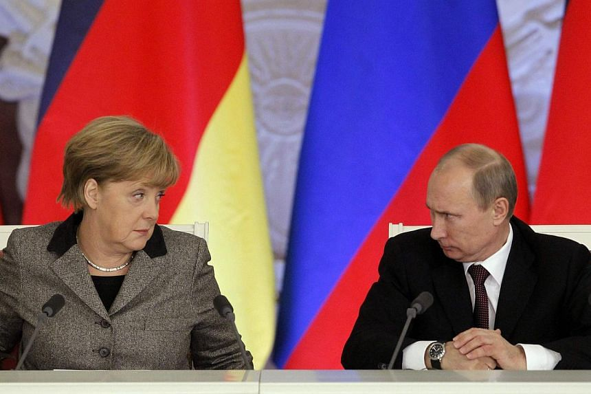 Russian President Vladimir Putin (right) and German Chancellor Angela Merkel look at each other while answering journalists' questions during a joint news conference in Moscow's Kremlin on Nov 16, 2012. -- FILE PHOTO: REUTERS