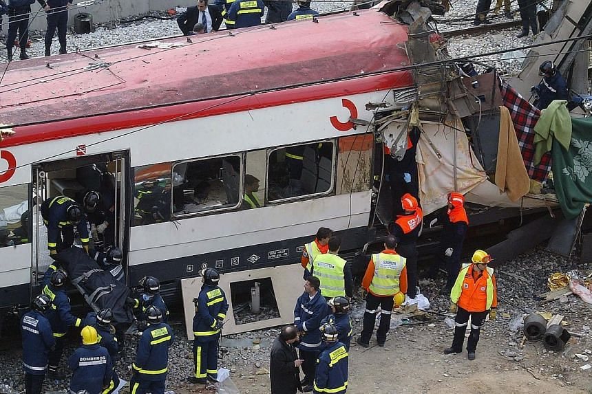Rescue workers evacuate the body of a victim following a terror bombing on a train at the Atocha railway station in Madrid on March 11, 2004.A decade after Al Qaeda-inspired bombers blew apart four Madrid commuter trains, killing 191 people, Sp