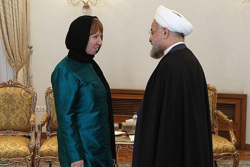 A handout picture released by the official website of the Iranian president shows the Islamic Republic's President Hassan Rouhani (right) meeting with European Union foreign policy chief Catherine Ashton on March 9, 2014, in Teheran.Iranian new