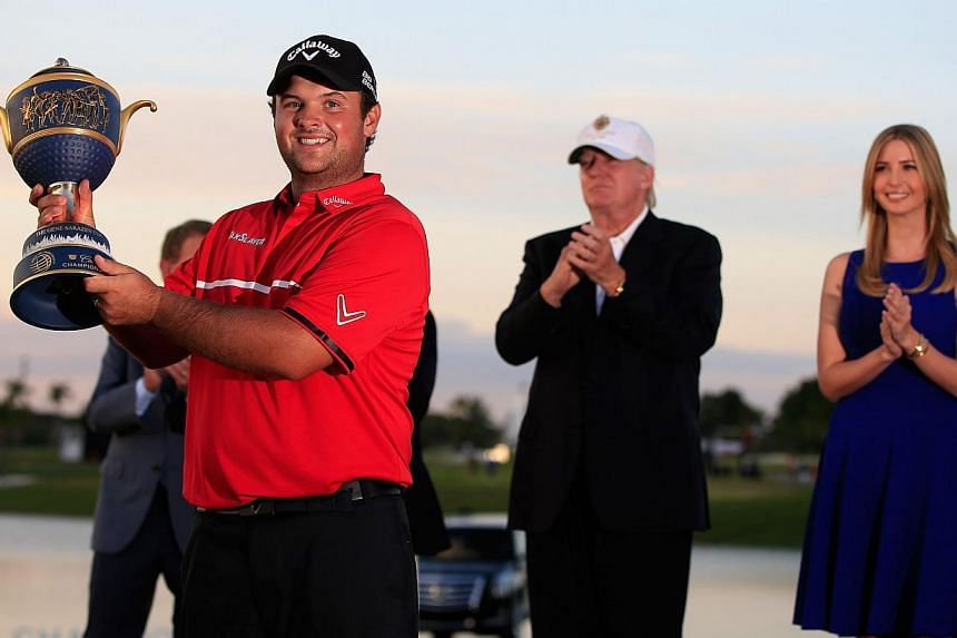 Patrick Reed celebrates with the Gene Sarazen Cup after his victory as Donald Trump and Ivanka Trump (right) look on during the final round of the World Golf Championships-Cadillac Championship at Trump National Doral on March 9, 2014 in Doral, Flori