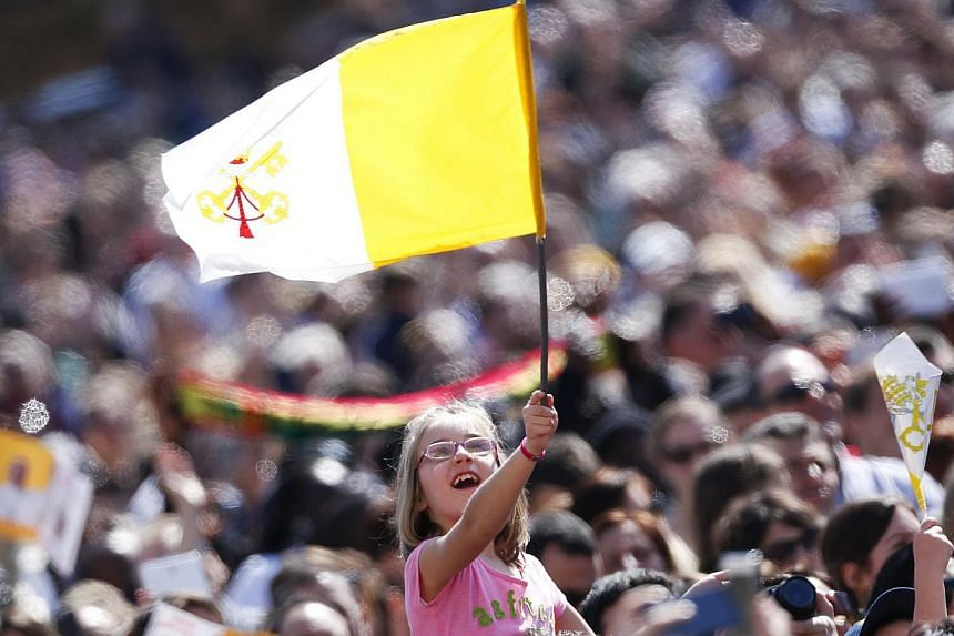 A girl waves the Vatican flag as Pope Francis leads the Angelus prayer in Saint Peter's Square at the Vatican on March 9, 2014. -- PHOTO: REUTERS
