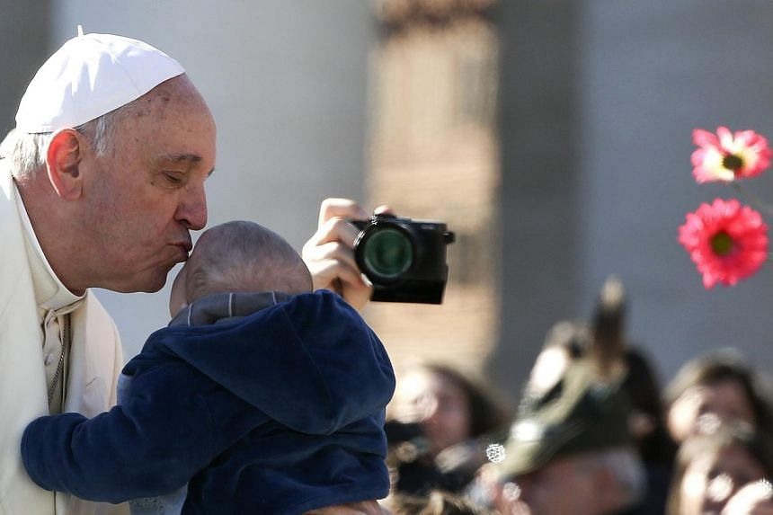 Pope Francis kisses a child as he arrives to lead the general audience in Saint Peter's Square at the Vatican on March 5, 2014. -- FILE PHOTO: REUTERS