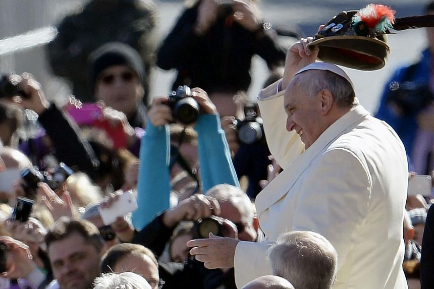 Pope Francis smiles as he wear a military Alpine hat upon his arrival at Saint Peter's Square for the weekly general audience on March 5, 2014. -- FILE PHOTO: AFP