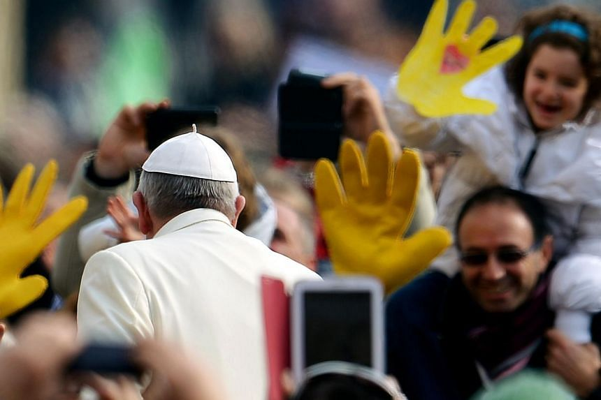 Pope Francis greets the crowd as he arrives for his general audience in Saint Peter's Square at the Vatican on Feb 26, 2014. -- FILE PHOTO: AFP