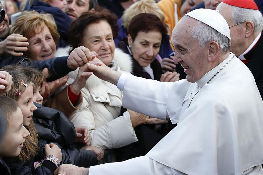 Pope Francis greets faithful as he arrives for his pastoral visit at the Saint Tommaso parish in the outskirts of Rome on Feb 16, 2014. -- FILE PHOTO: REUTERS