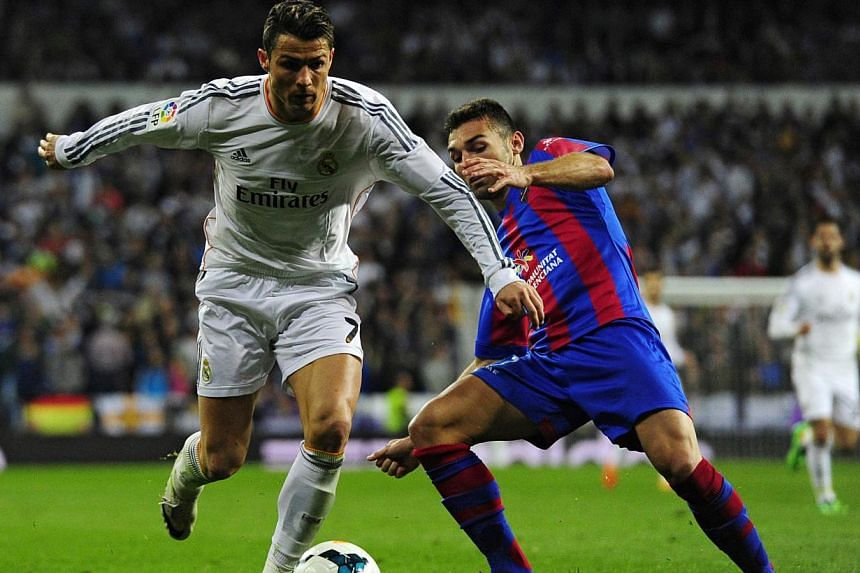 Real Madrid's Portuguese forward Cristiano Ronaldo (left) vies with Levante's midfielder David Barral during the Spanish league football match Real Madrid CF vs Levante UD at the Santiago Bernabeu stadium in Madrid on March 9, 2014. -- PHOTO: AFP&nbs