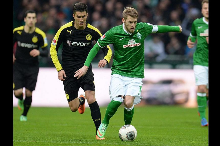 Bremen's midfielder Aaron Hunt (right) and Dortmund's midfielder Nuri Sahin vie for the ball during the German first division Bundesliga football match Weder Bremen vs Borussia Dortmund in Bremen, northern Germany on Feb 8, 2014. Hunt has been h
