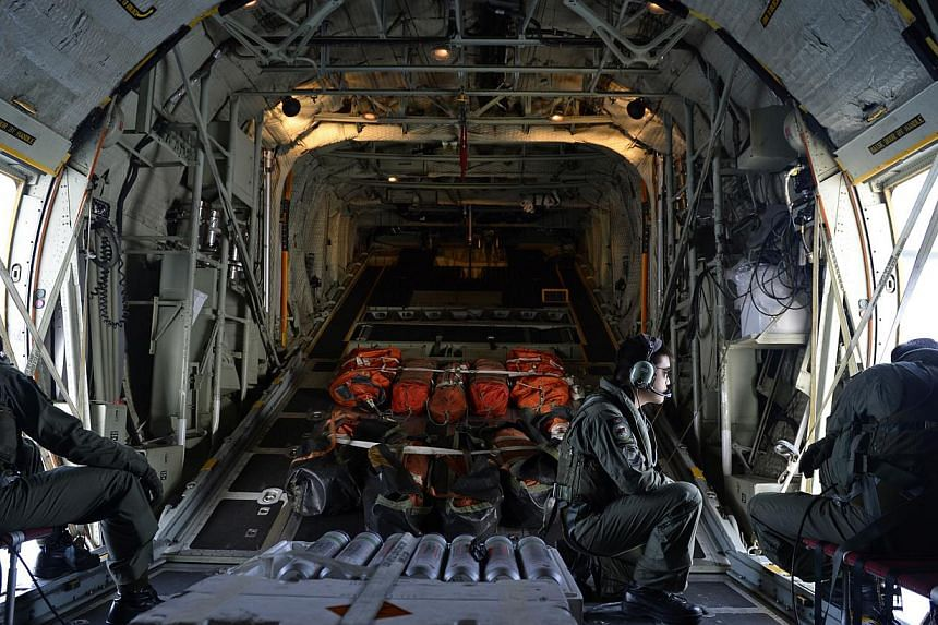 RSAF personnel on board a C-130 scanning the seas about 140 nautical miles north-east of Kota Bahru, Kelantan, for any signs of the missing Malaysian Airlines plane on March 9, 2014. Ten inflatable rafts (orange bundles at the back of the plane) were