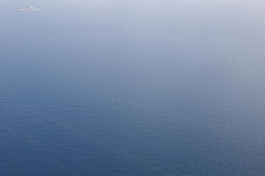 A ship (top left in photo) in the waters of the South China Sea seen from a Republic of Singapore Air Force C-130 plane on March 9, 2014. The vastness of the sea was such that it was often hard to make out whether the boats in the water were search-a