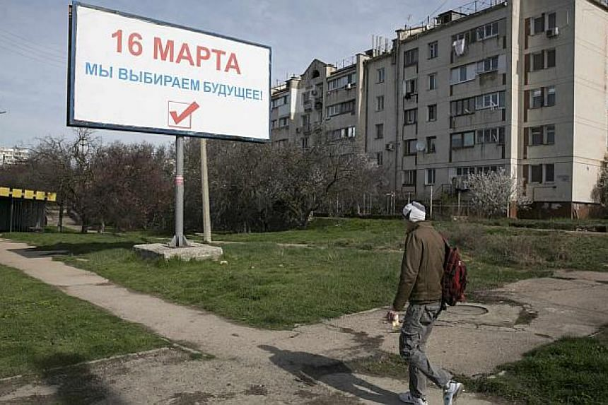 """A man walks near a poster that reads, """"On March 16, we are choosing our future"""" ahead of a March 16 referendum in the Crimean port city of Sevastopol on March 10, 2014.The United States would support greater autonomy for Crimea as long as this"""