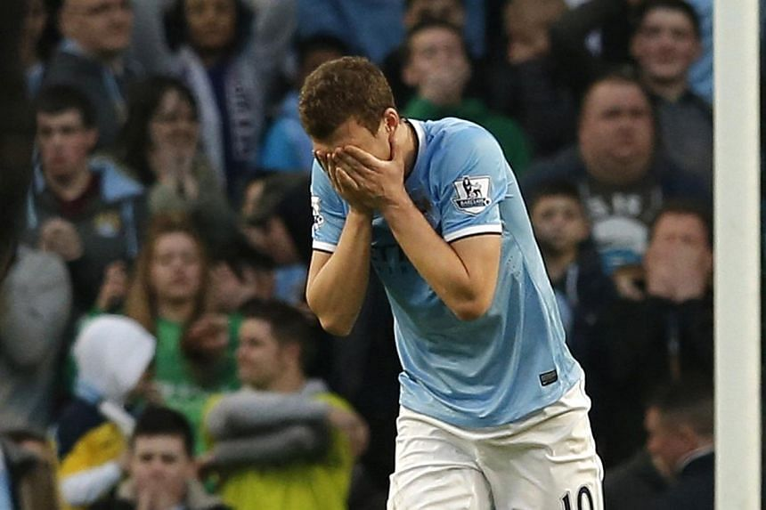 Manchester City's Edin Dzeko reacts after a missed opportunity during their English FA Cup quarter final soccer match against Wigan Athletic at the Etihad stadium in Manchester, northern England, on March 9, 2014. -- PHOTO: REUTERS