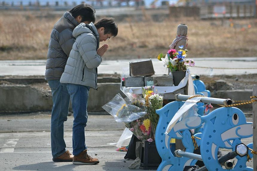 People pray for victims of March 11 massive earthquake and tsunami atthe former disaster control centre in Minamisanriku, Miyagi prefecture on March 9, 2014 two days before the third anniversary of March 11, 2011 earthquake and tsunami. -- FILE PHOTO