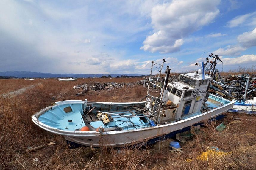 Fishing boats sit grounded on land three years after the disaster in Namie, near the striken Tepco Fukushima Dai-ichi nuclear plant in Fukushima prefecture on March 10, 2014, one day before the third anniversary of the massive earthquake and tsunami