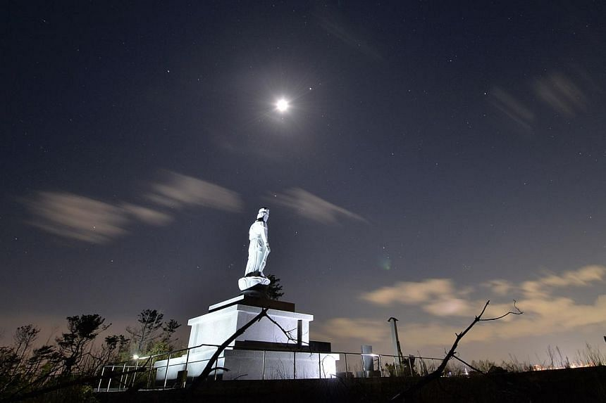 A Buddhist statue erected to honour Japan's tsunami victims is seen on the seashore one day before the third anniversary of the country's March 11 earthquake and tsunami in the Arahama district of Sendai, Miyagi prefecture. -- PHOTO: AFP