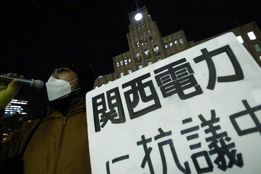 An anti-nuclear protester holds a placard in front of a branch of Kansai Electric Power Co, the operator of the Ohi nuclear power plant which has been shut down, in Tokyo on March 10, 2014, a day before the third anniversary of the March 11, 2011 ear