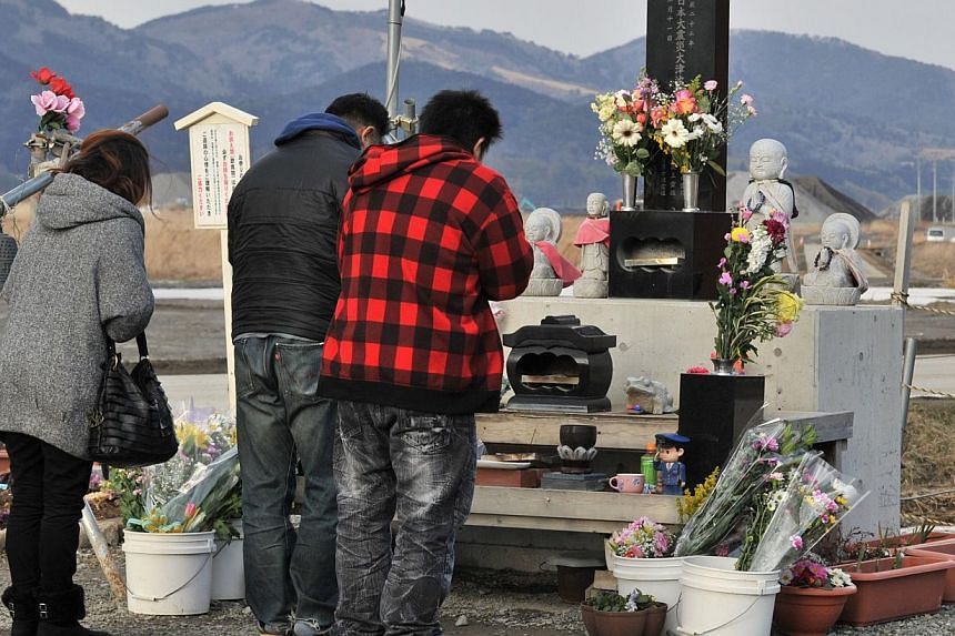People pray at a cenotaph for tsunami victims at Okawa elementary school in Ishinomaki, Miyagi prefecture on March 10, 2014, before the third anniversary of the earthquake and tsunami on March 11, 2011.-- PHOTO: AFP