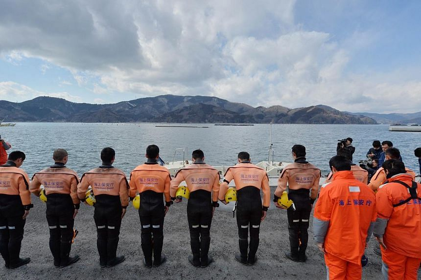 Divers of a Japanese Coast Guard marine rescue unit observe a moment of silence before they search waters in the hope of finding missing persons at Tsukahama coastal area in Onagawa, Miyagi prefecture on March 10, 2014, one day before the third anniv