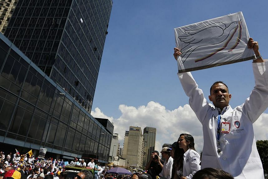An anti-government doctor holds up a placard with a picture of a peace dove during a march to demand medical supplies for hospitals in Caracas on March 10, 2014. -- PHOTO: REUTERS