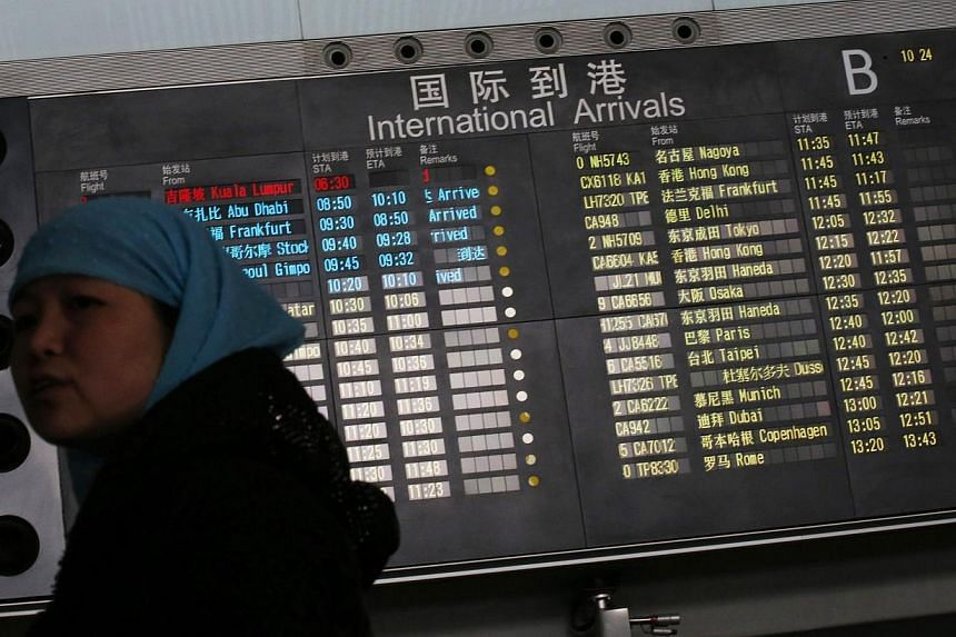 A woman stands in front of a flight information board displaying the Scheduled Time of Arrival (STA) of Malaysia Airlines flight MH370 (top, in red) at the Beijing Capital International Airport in Beijing, on March 8, 2014. -- FILE PHOTO: REUTERS