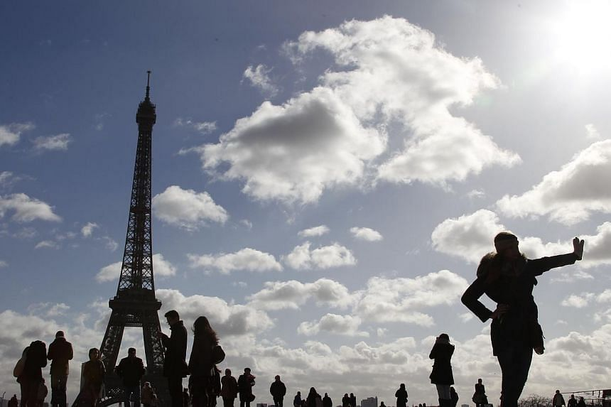 Tourists on the Trocadero, in front of the Eiffel tower, in Paris on Feb 7, 2014. -- FILE PHOTO: AFP