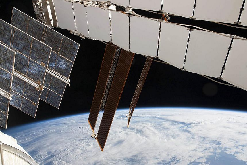 NASA photo of Solar array panels on the Russian segment of the International Space Station and a blue and white part of Earth. -- FILE PHOTO: REUTERS