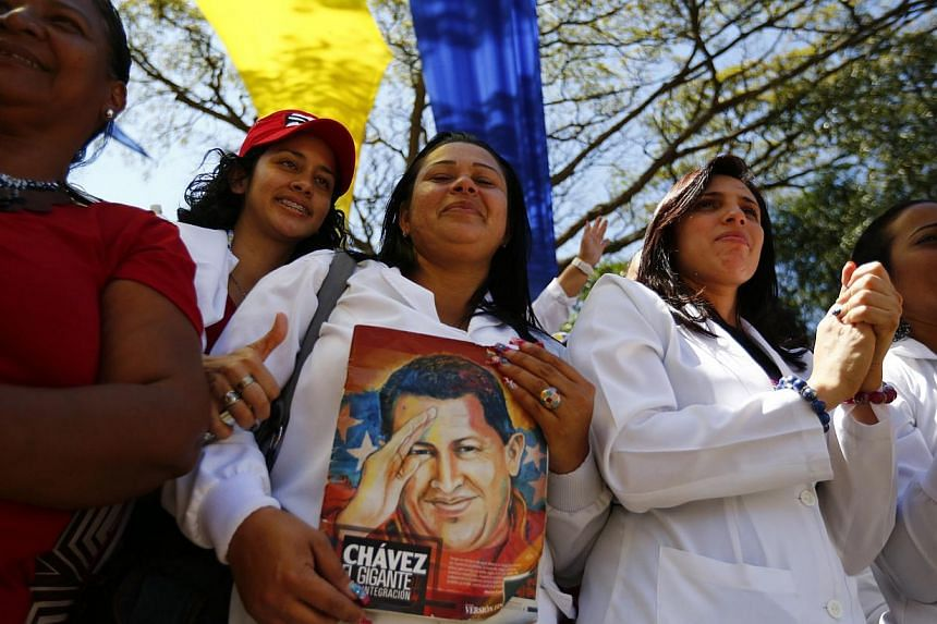 Venezuela's community doctors hold a picture of Venezuela's late President Hugo Chavez as they attend a graduation at Miraflores palace in Caracas on March 10, 2014. -- PHOTO: REUTERS