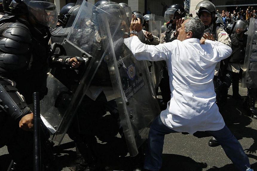 National policemen scuffle with an anti-government doctor during a march to demand medical supplies for hospitals in Caracas on March 10, 2014. -- PHOTO: REUTERS