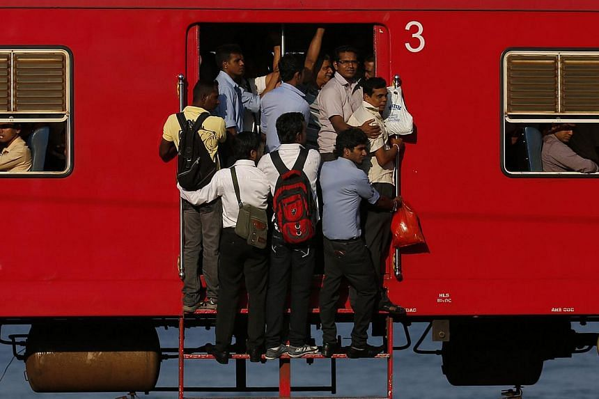 People hang onto a crowded local passenger train as they travel to Colombo, Sri Lanka, on March 11,2014. -- PHOTO: REUTERS