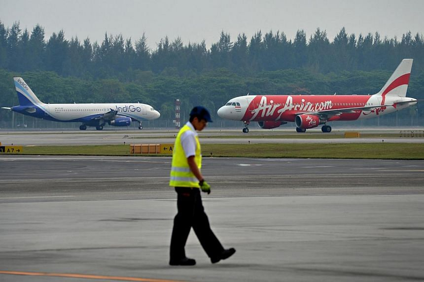 Air Asia and IndiGo planes on Changi airport runway.Giving Changi Airport a third runway is proving more challenging than expected. -- ST PHOTO: NURIA LING