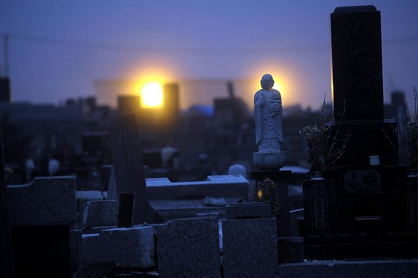 EERIE STILLNESS: As dusk falls on Ishinomaki, Miyagi Prefecture, street lamps illuminate a graveyard outside a temple that is packed with toppled headstones which are mostly damaged and strewn haphazardly against one another. Clean-up crews have been