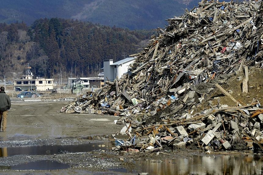 TRASH MOUNTAIN: At Rikuzentakata, Iwate Prefecture, a mountain of debris about 5.5m high has been cleared to the side of the road as part of the rebuilding efforts in the areas hit by the giant waves. Iwate Prefecture has 4.8 million tonnes of debris