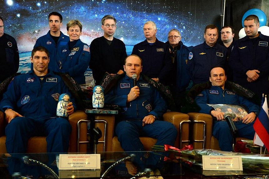 Wearing traditional Kazakh costumes US astronaut Michael Hopkins (left) sits together with Russia's cosmonauts Oleg Kotov (centre) and Sergey Ryazansky (right), as they attend a press conference in Karaganda, Kazakhstan, on March 11, 2014, some hours