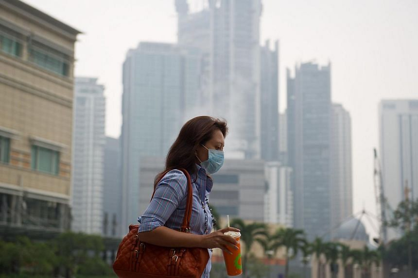 A woman wears a face mask as haze start to shrouds Kuala Lumpur on March 4, 2014. -- FILE PHOTO: AFP